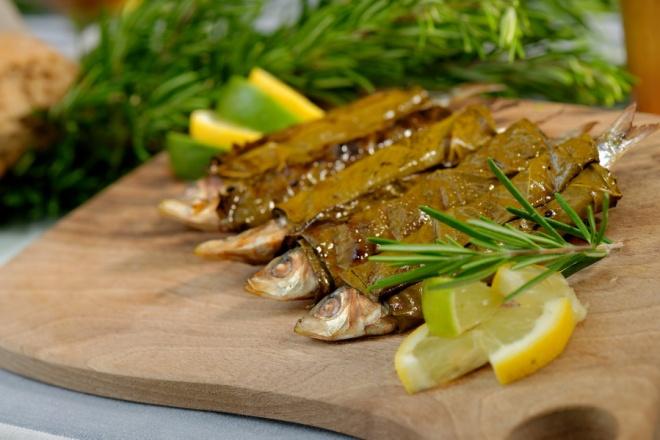 Grilled sardine fish wrapped in vine leaves, served with lemon and rosemary_resize